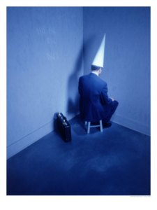 Businessman-Sitting-in-Corner-with-Dunce-Hat-Photographic-Print-C12695082