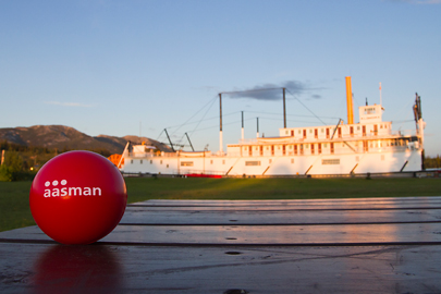 Aasman red ball in front of historic paddlewheeler in Whitehorse, Yukon