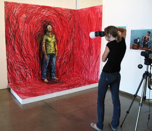 Alexa Meade photographing her painting of a man with red background